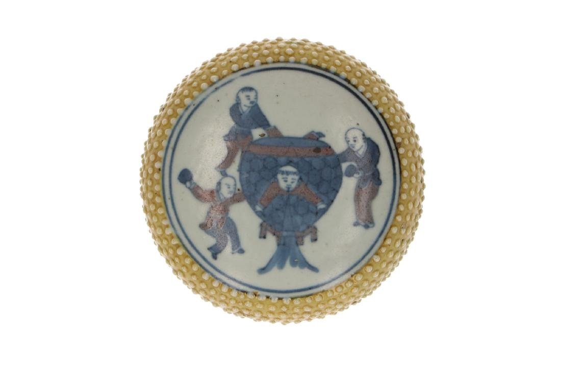 A polychrome porcelain lidded circular box with a