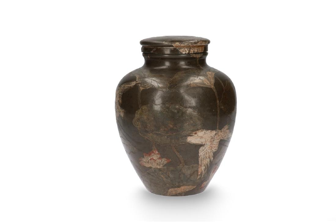 A pewter lidded vase with a carved and painted decor of