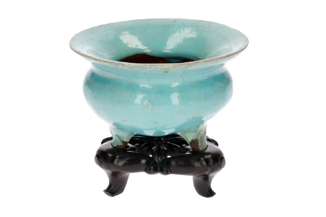 A turquoise glazed stoneware tripod censer on wooden
