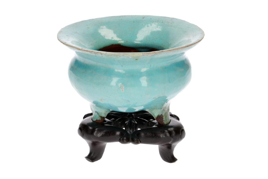 A turquoise glazed stoneware tripod censer on wooden