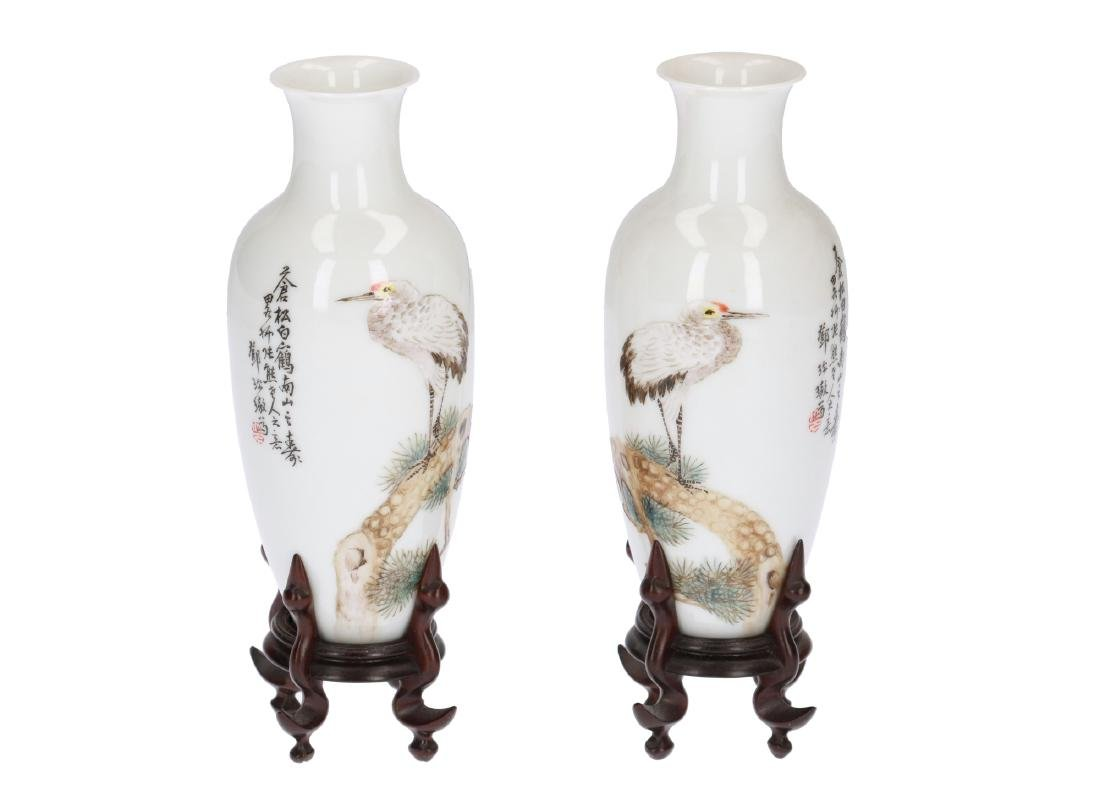 A pair of polychrome eggshell porcelain vases on wooden