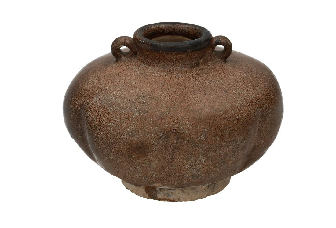 A brown glazed ceramic vase with two grips and a lobbed