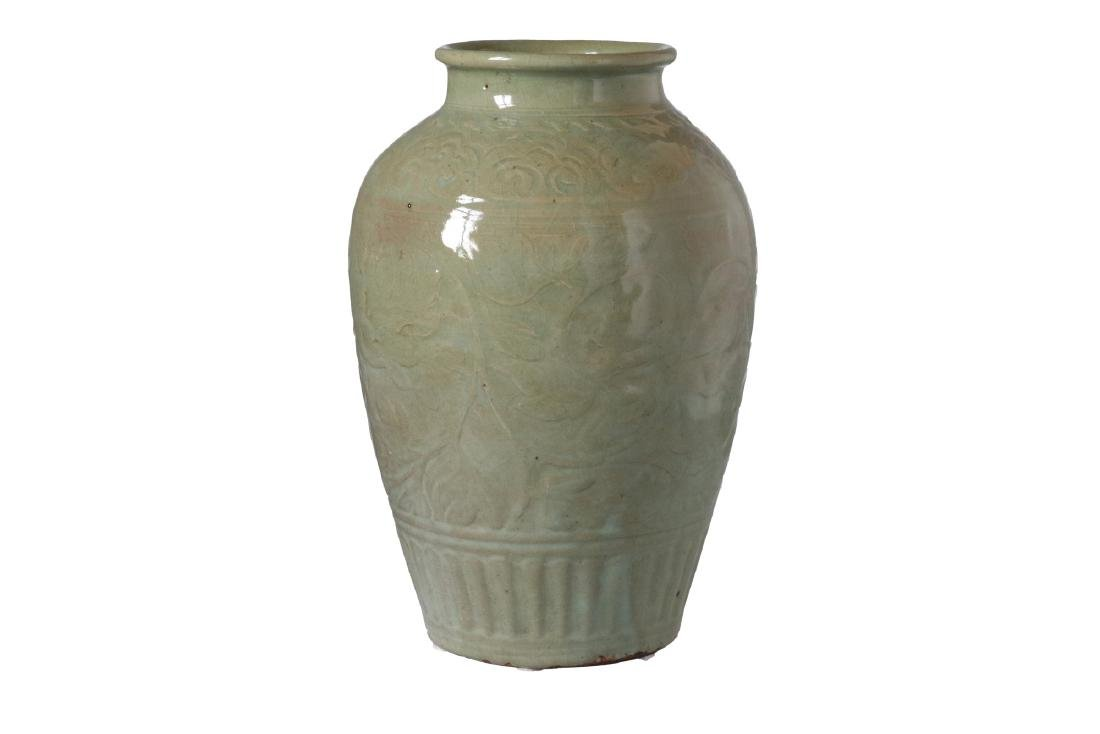 A green glazed celadon vase with relief decor of