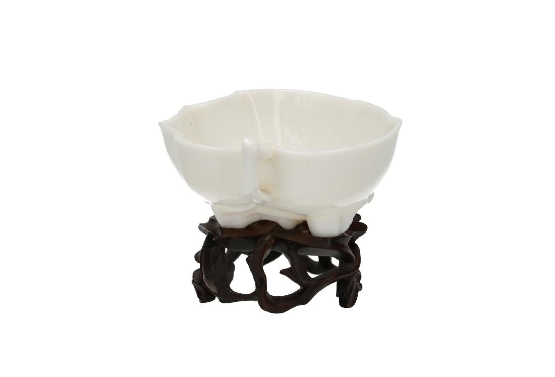 A Blanc-de-Chine porcelain cup with wooden stand, both