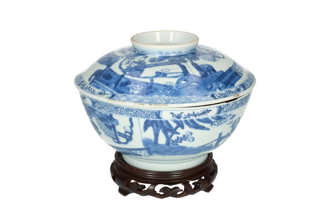 A blue and white porcelain lidded bowl on wooden base,