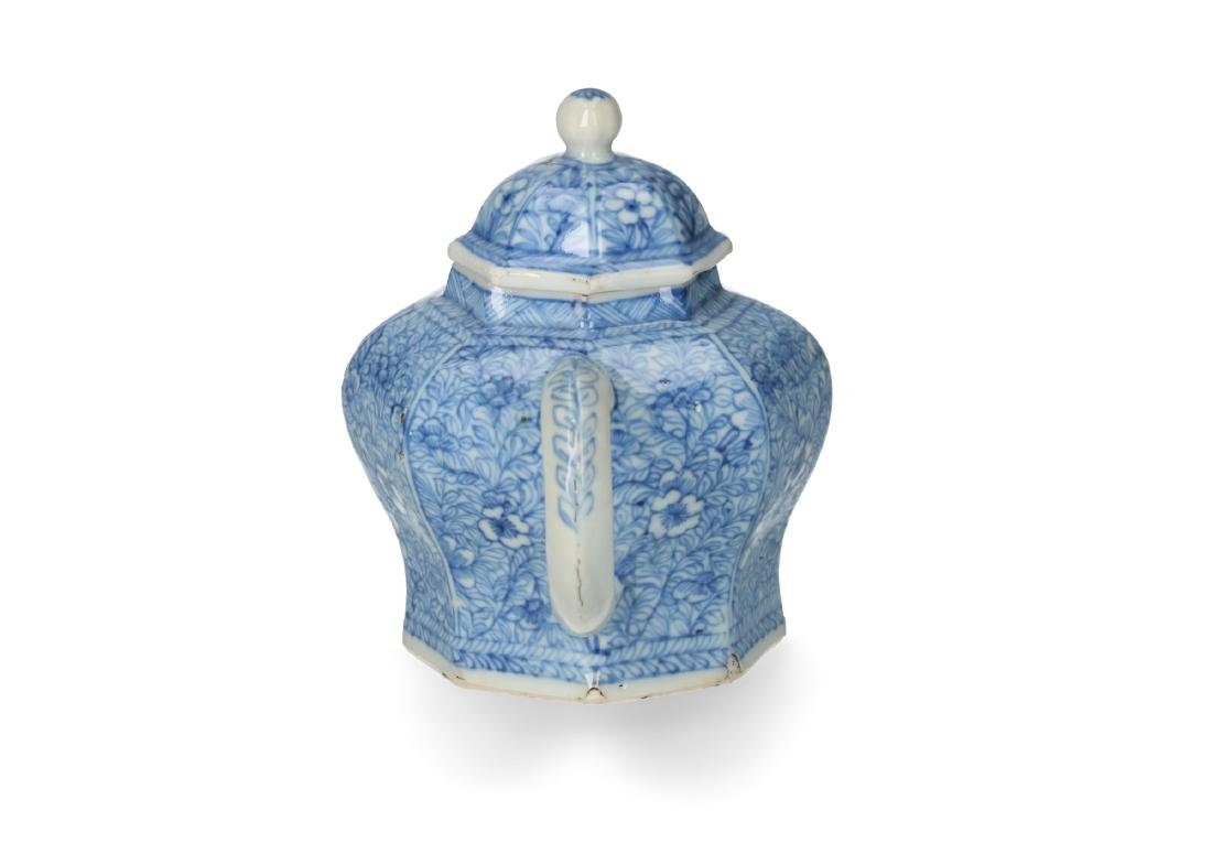A blue and white porcelain teapot with floral decor.