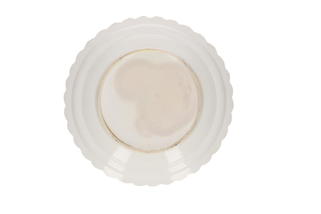A blue and white porcelain dish with scalloped rim and