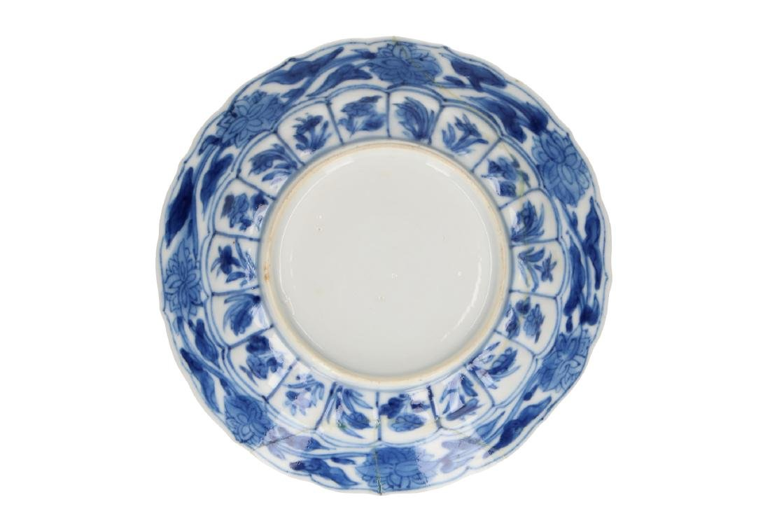A blue and white porcelain saucer with scaloped rim,