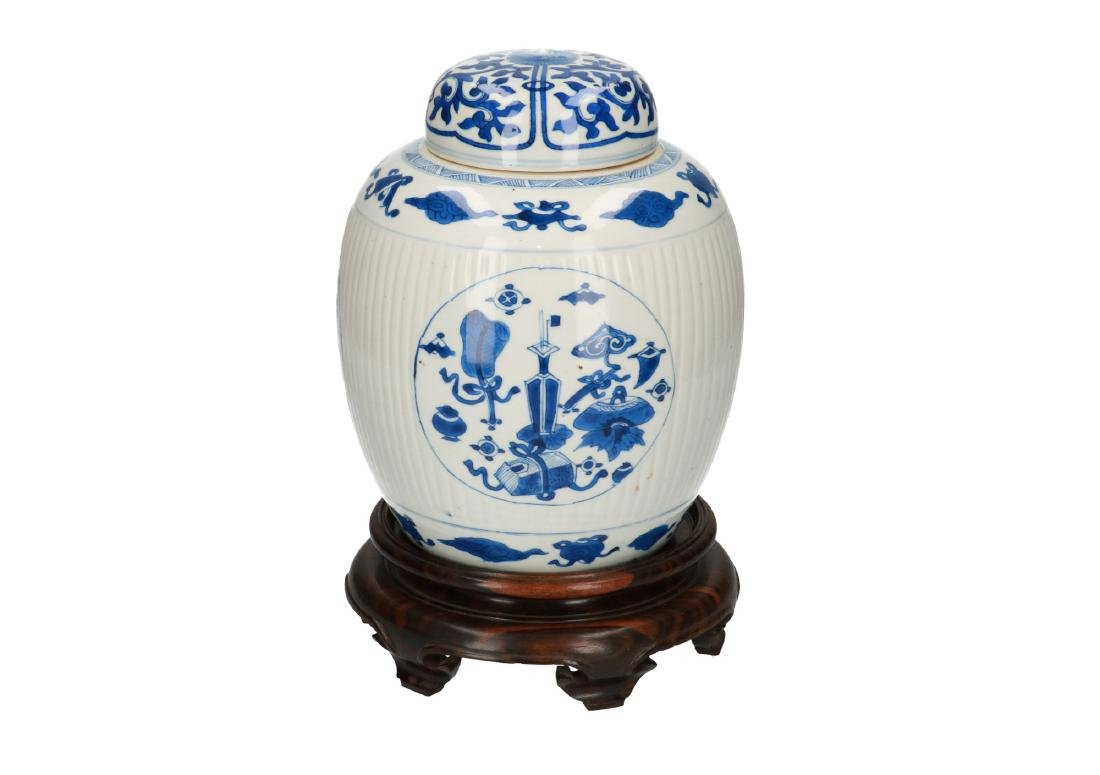 A blue and white porcelain ribbed lidded jar on wooden