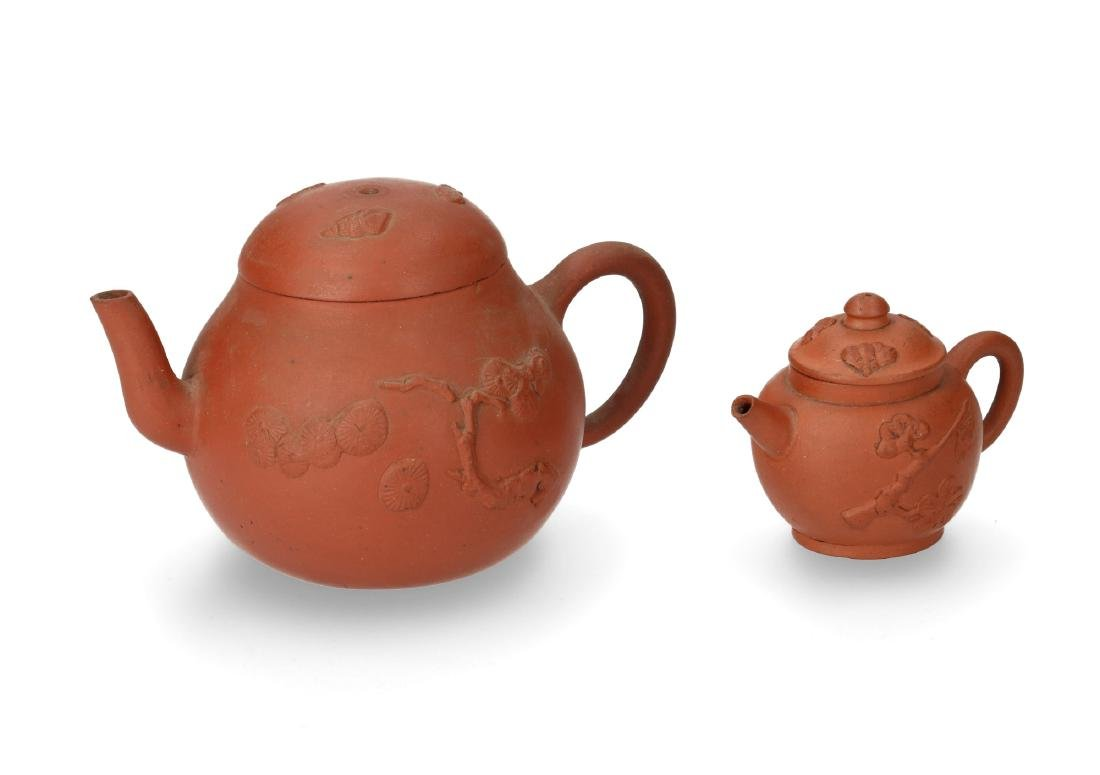 Lot of two Yixing teapots with relief decor. Both