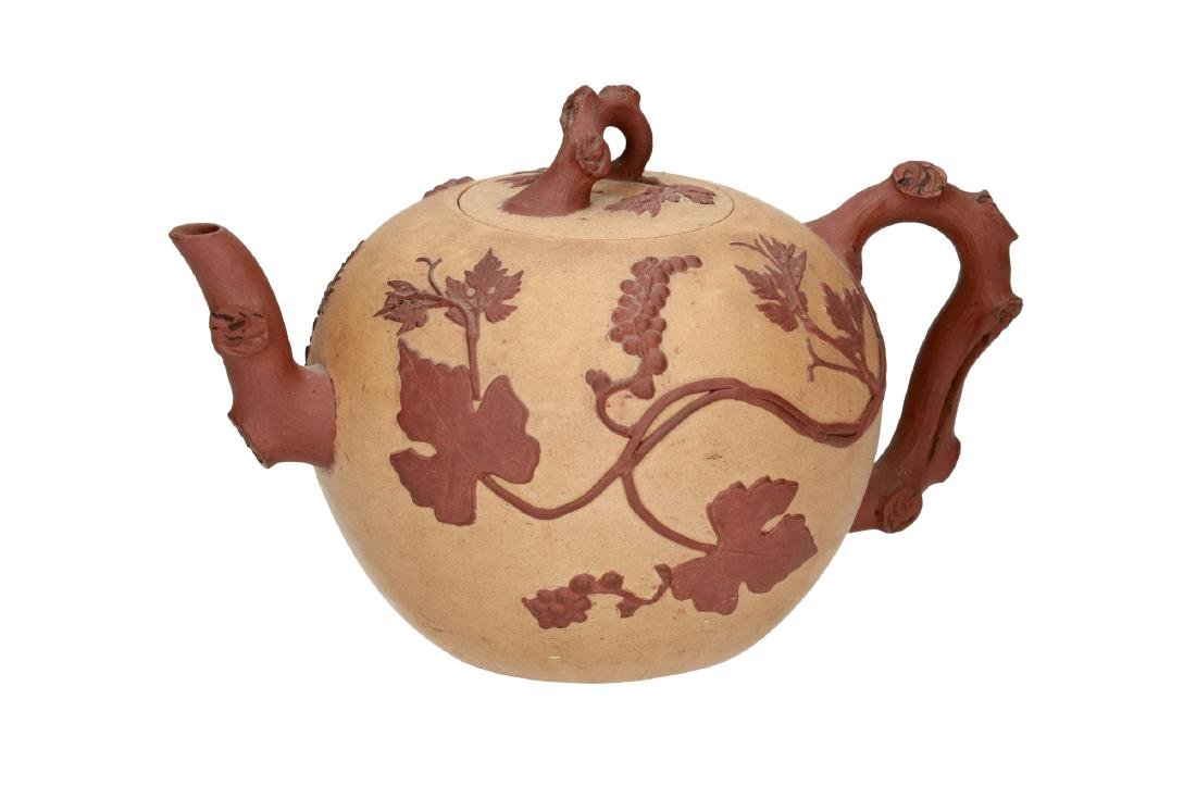 A Duan Ni Yixing teapot with relief decor of leaves and