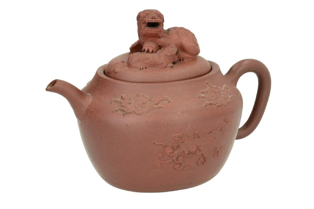 A purple terracotta Yixing teapot with relief decor of