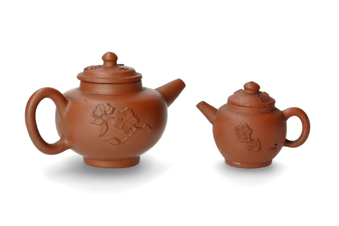A lot of two Yixing teapots with relief decor of