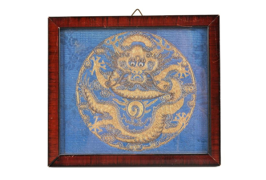 A framed textile medallion with gold decor of a dragon.