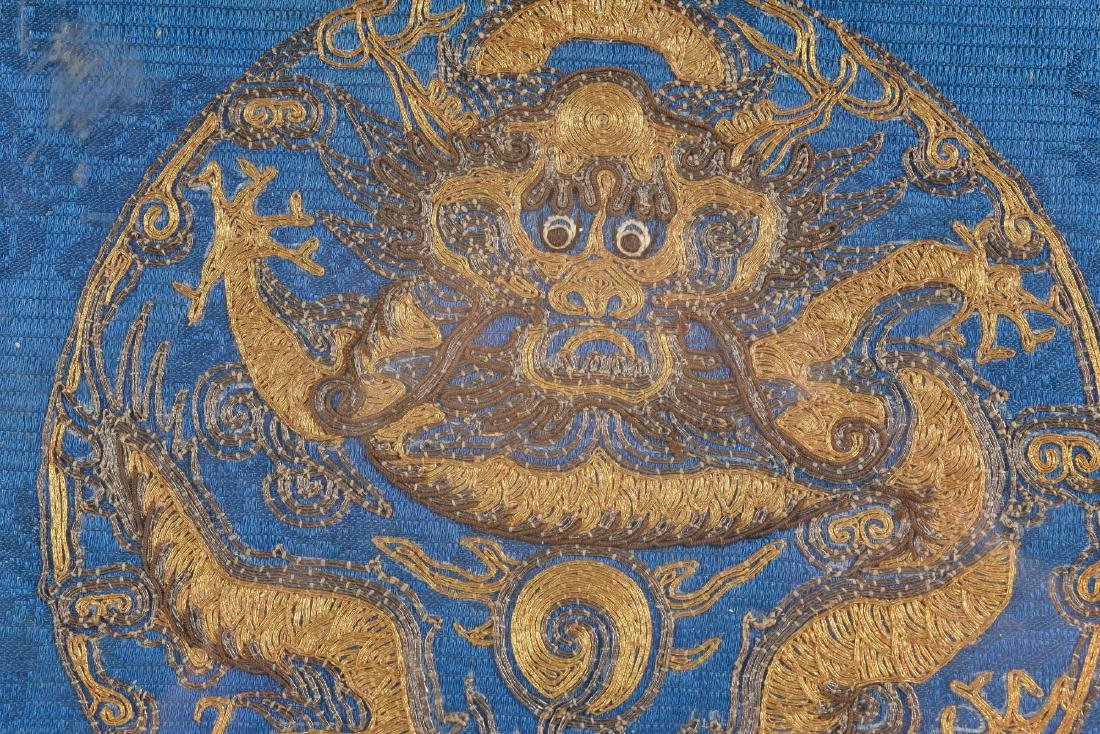 A framed textile medallion with gold decor of a dragon. - 2