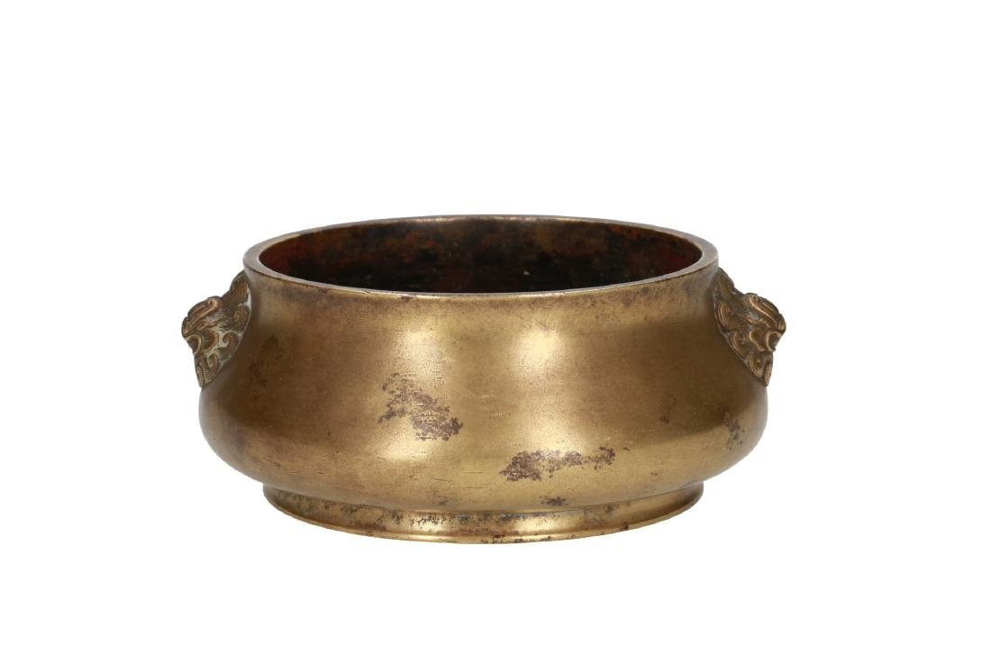 A bronze 'dragon' censer on a ring, with two mask