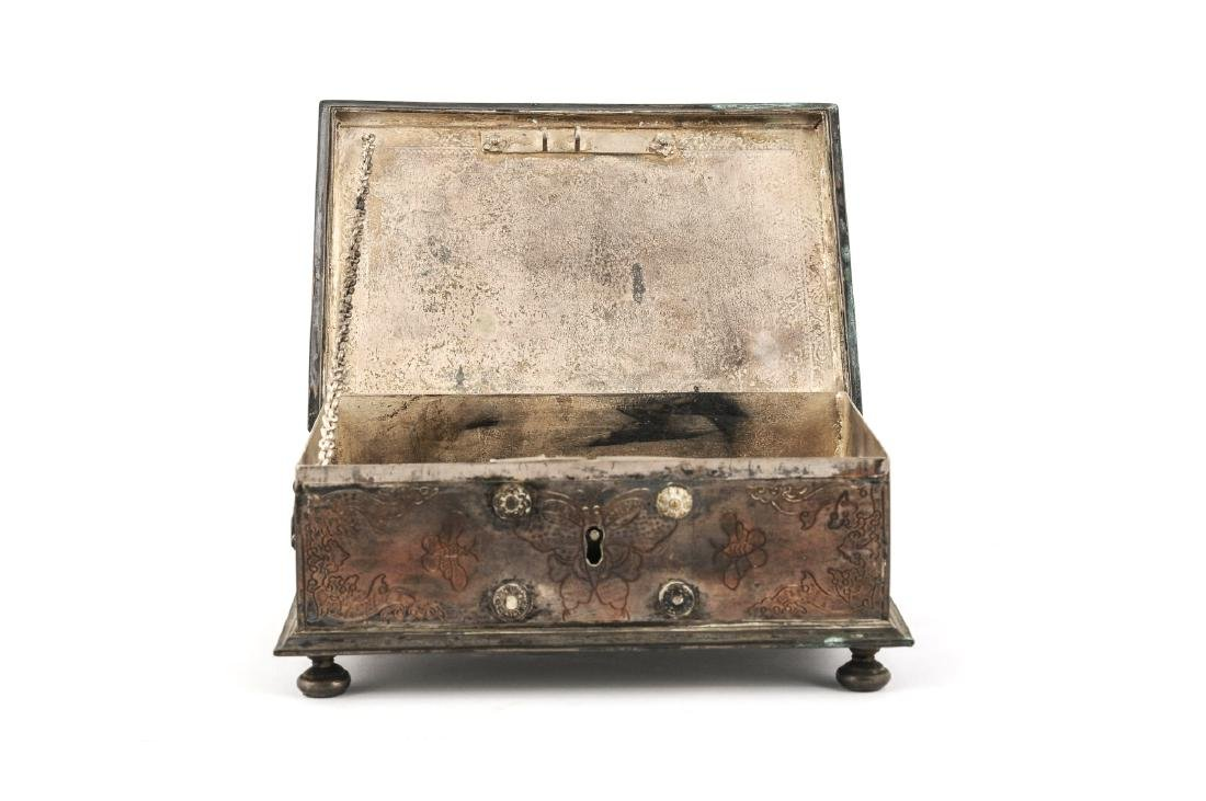A copper silver plated chest box on four legs,