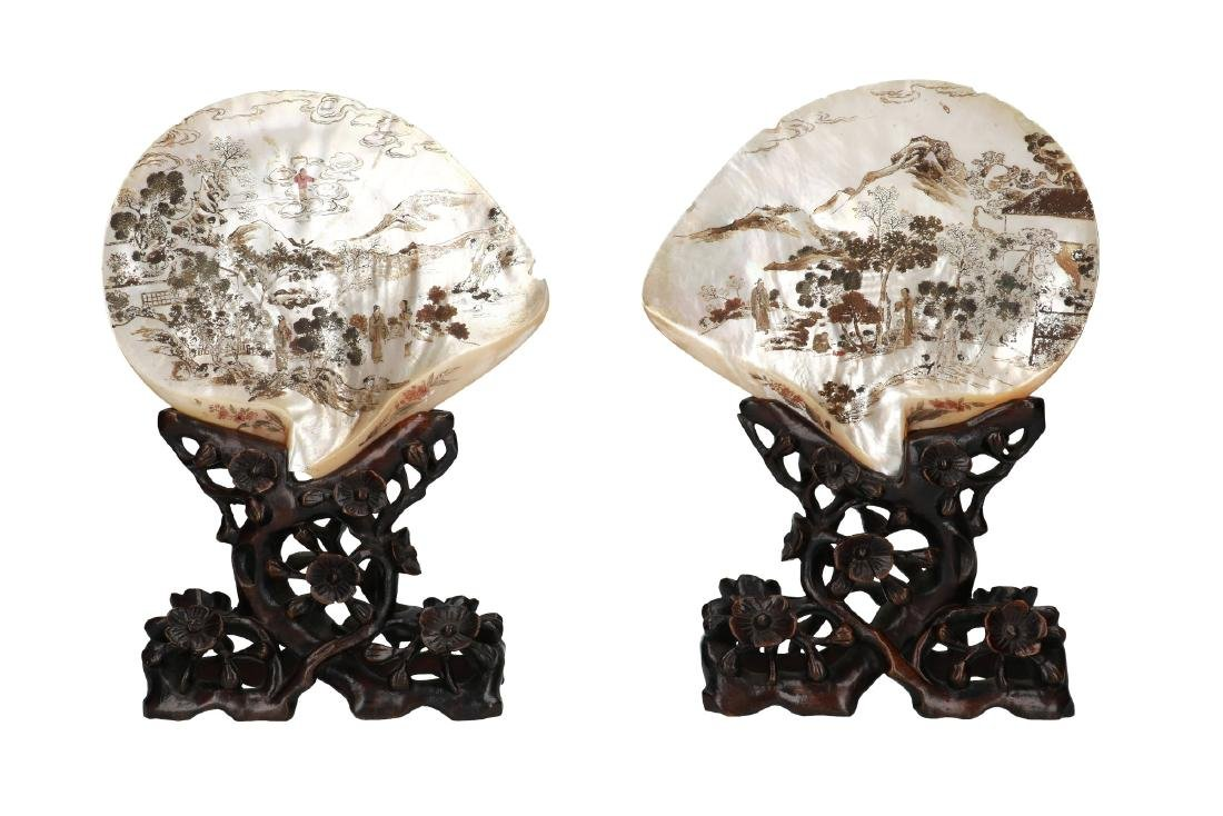 A pair of two shells engraved with a mountainous
