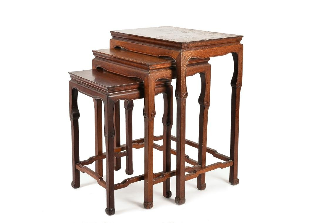 A set of three wooden tables, inlaid with decor of