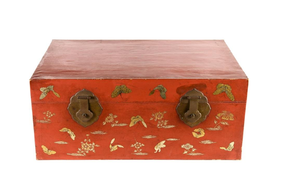 A red leather chest with gilded decor of butterflies