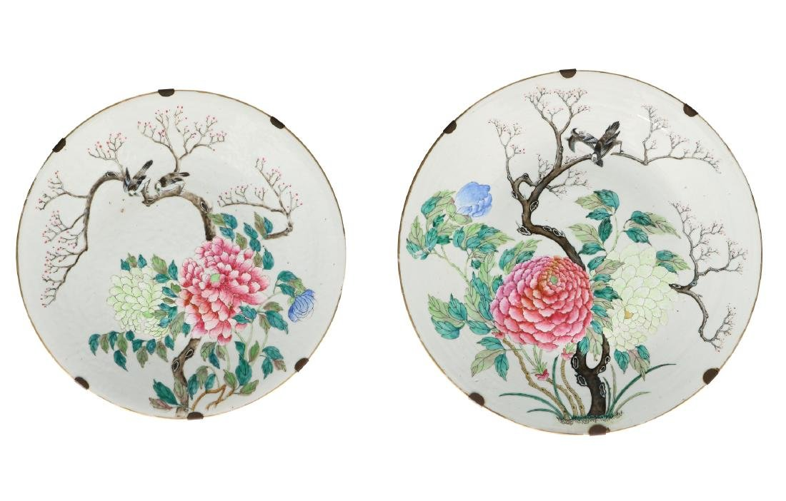 A pair of polychrome porcelain chargers, decorated with