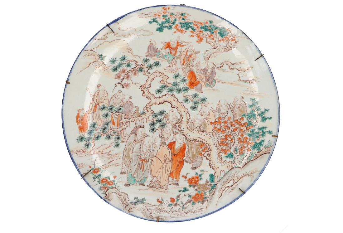 A large polychrome porcelain charger, decorated with 22