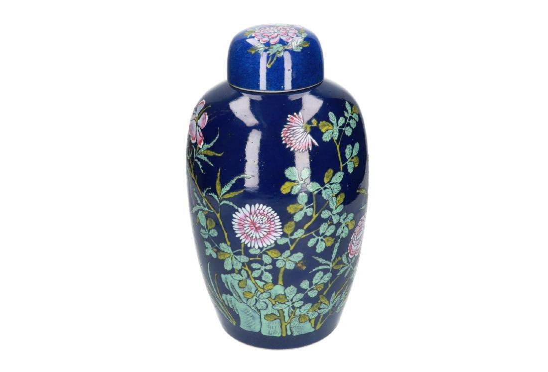 A powder-blue lidded vase with polychrome floral decor.