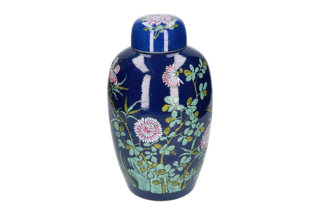 A powder-blue lidded vase with polychrome floral decor.
