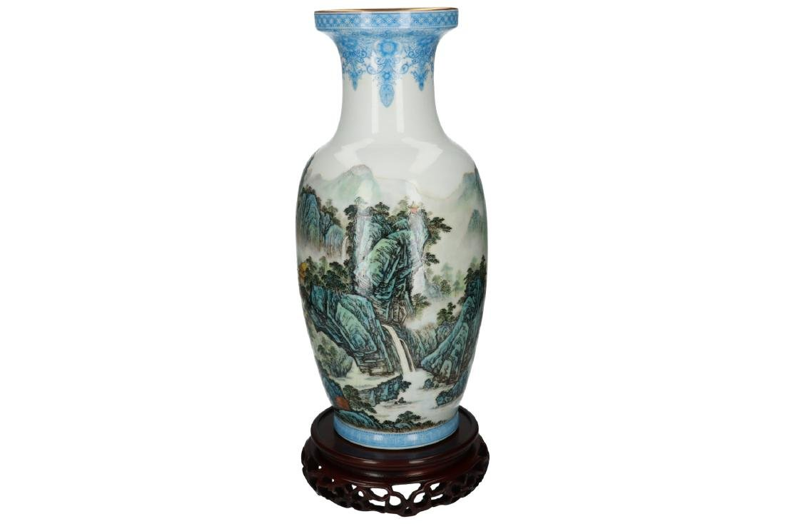 A polychrome porcelain vase on wooden base, decorated