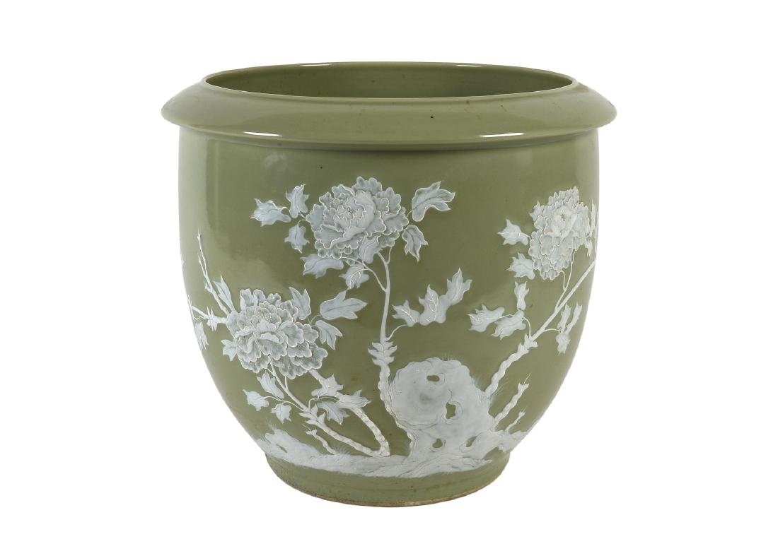 A large celadon porcelain cachepot with white relief