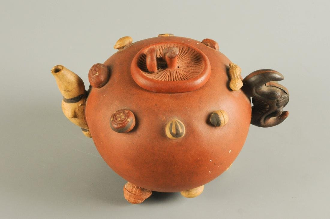 A Yixing teapot, decorated in relief with peanuts and