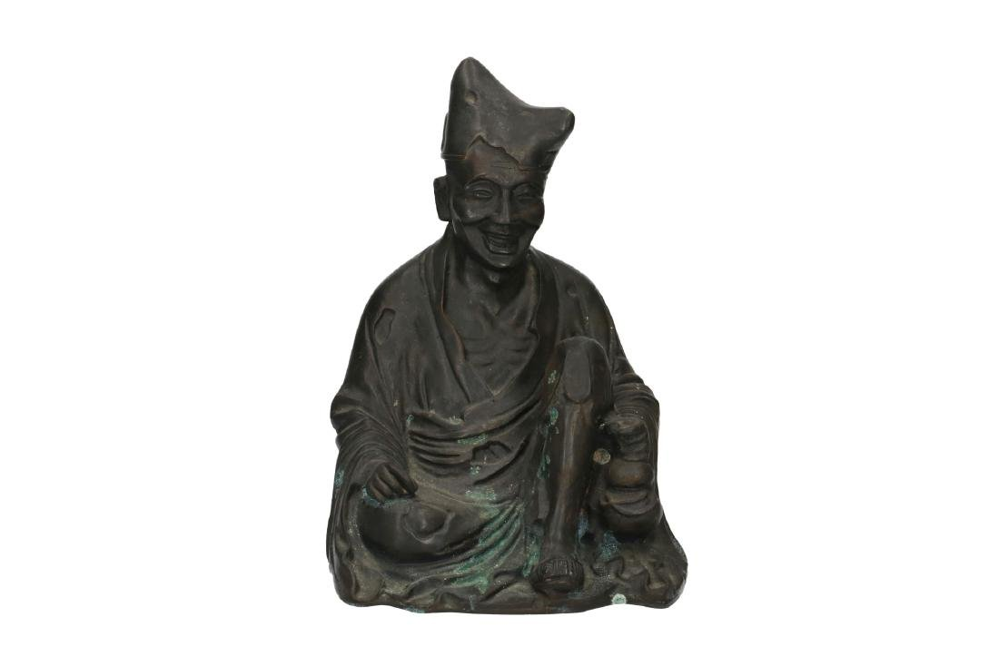 A bronze sculpture depicting a sitting man. Marked with