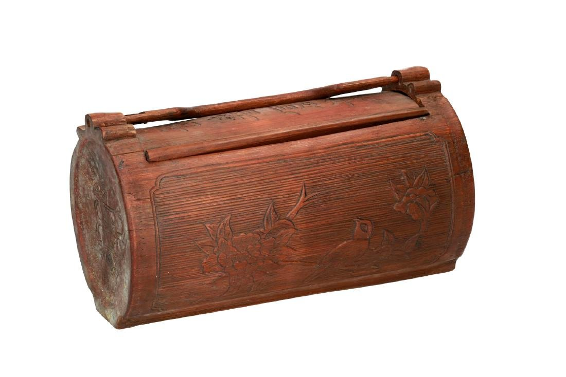 A wooden box with handle, decorated with flowers and