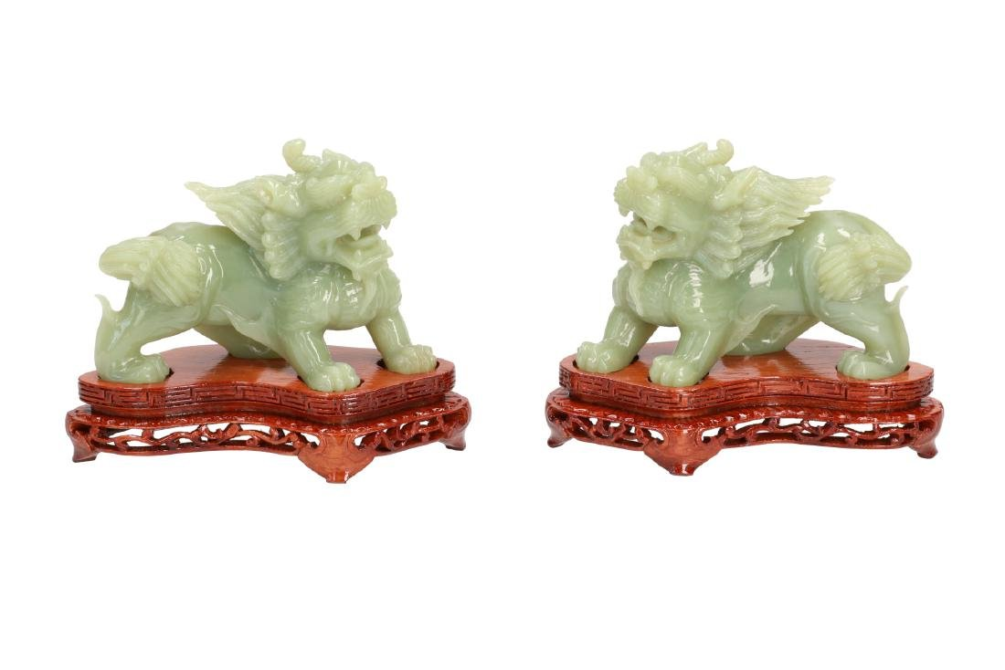 A pair of carved jade sculptures depicting lions.