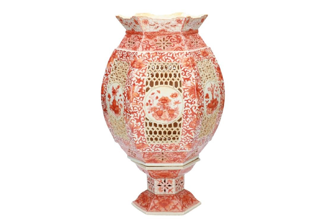 An iron red porcelain lantern with floral decor.