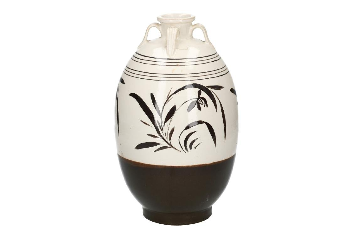 A black and white ceramic vase decorated with flowers.