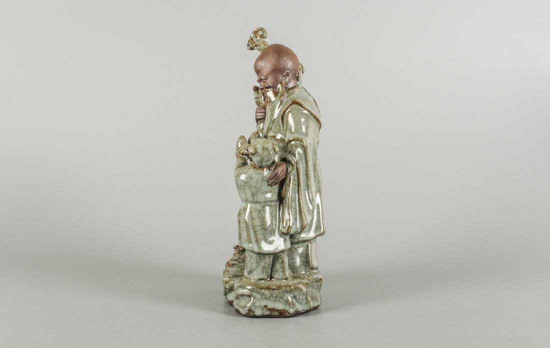 A glazed ceramic sculpture depicting an old man and a - 2