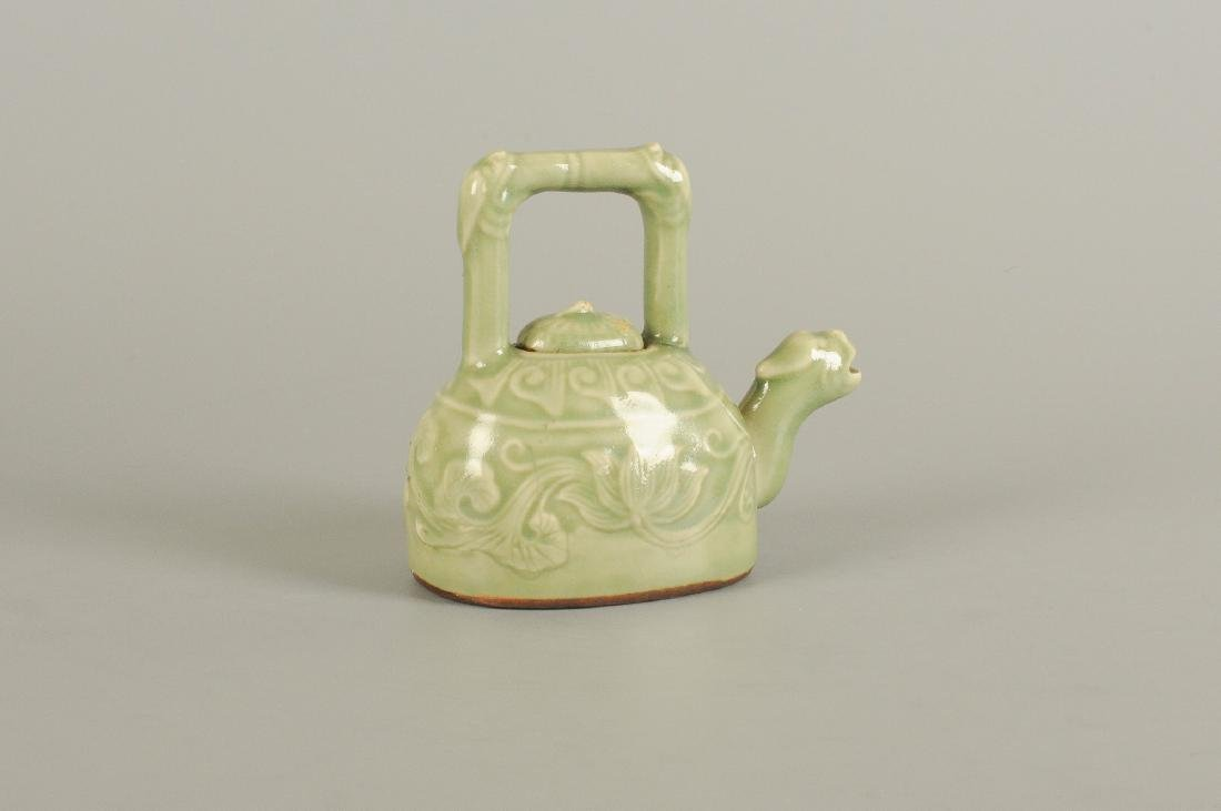 A celadon stoneware teapot. The spout in the shape of
