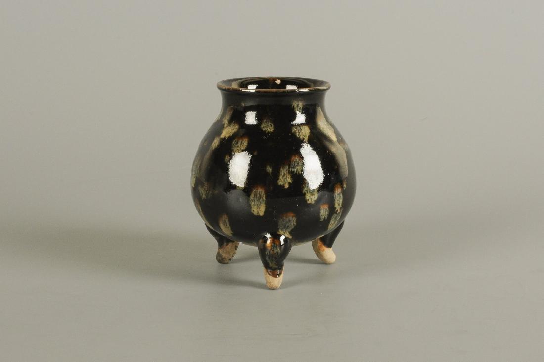 A polychrome stoneware jar standing on tripod,