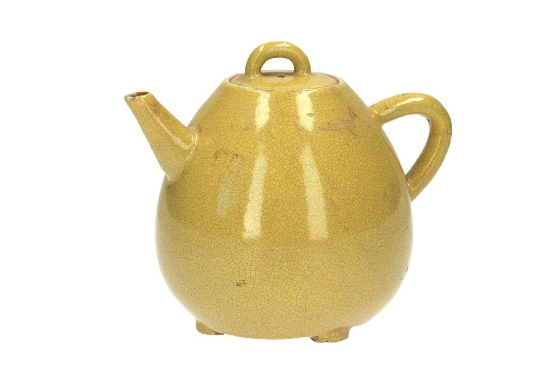 A yellow glazed porcelain teapot, standing on four