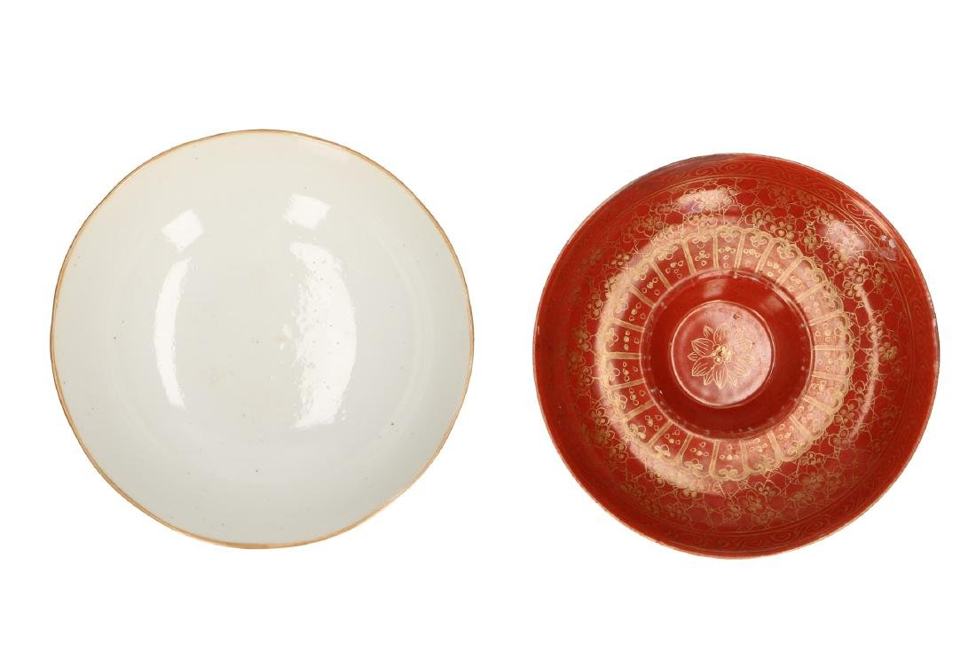 A lot of two coral red bowls, of which one standing on