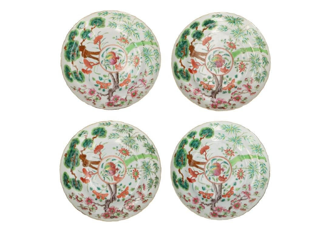 A set of four polychrome porcelain plates, decorated