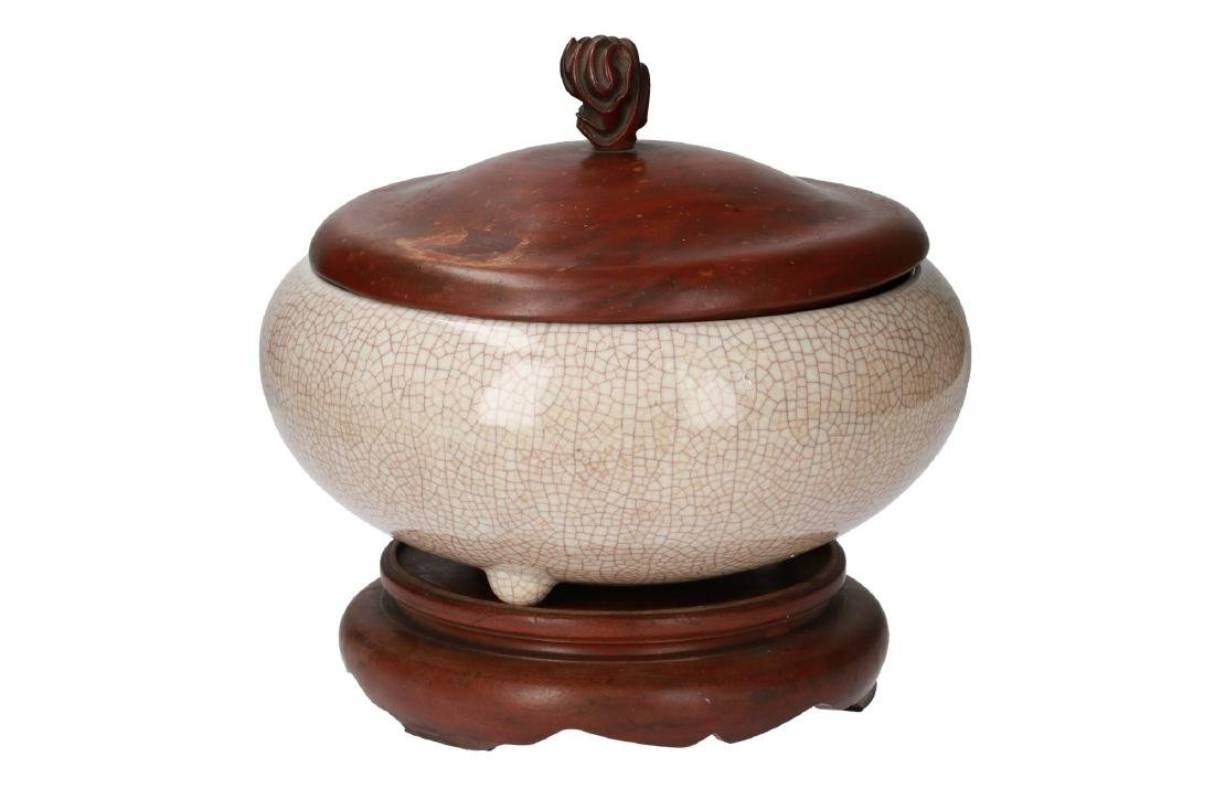 A cream glazed lidded jar wit wooden lid and stand.