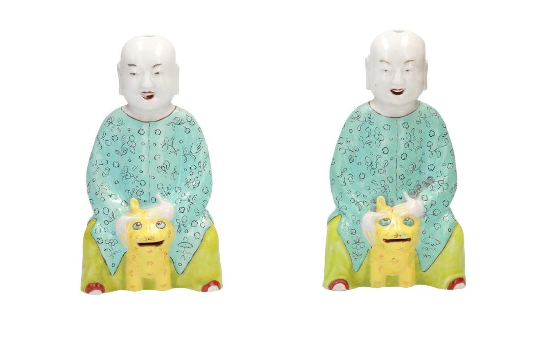 A pair of polychrome porcelain sculptures of boys with