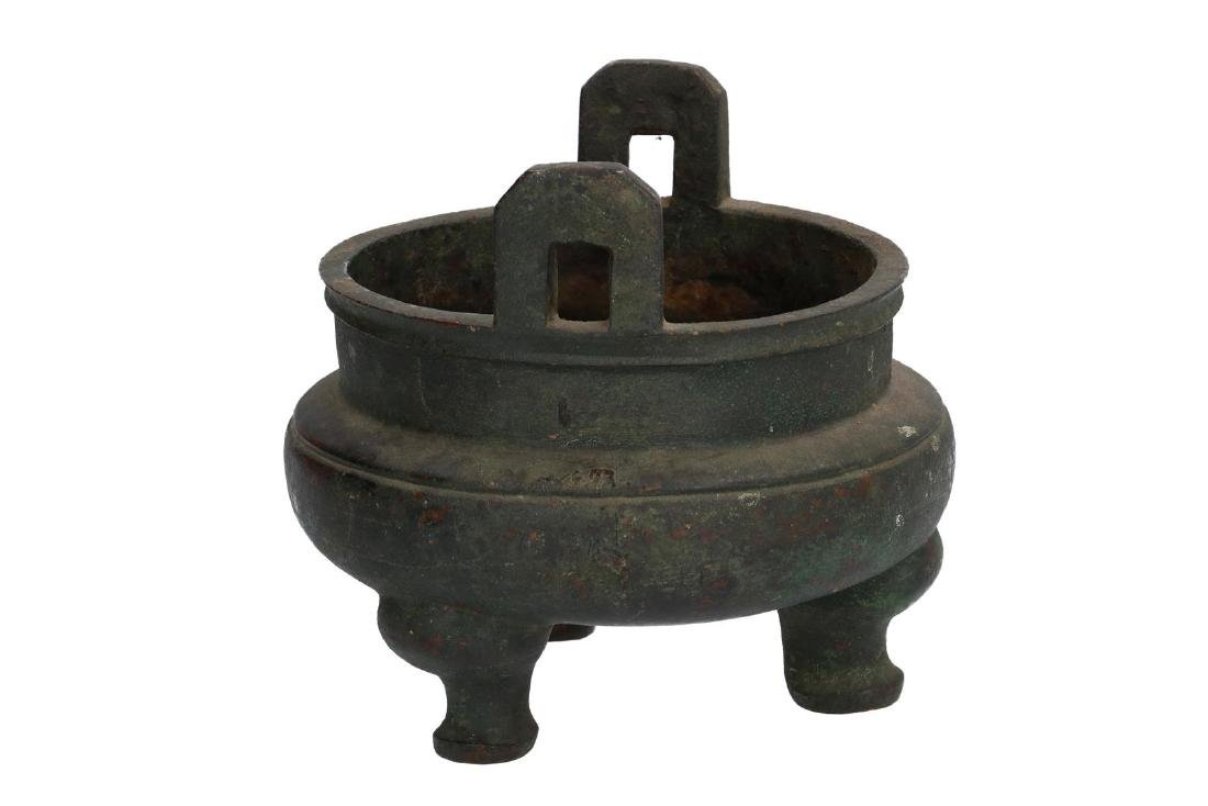 A bronze tripod censer with carved ring around the
