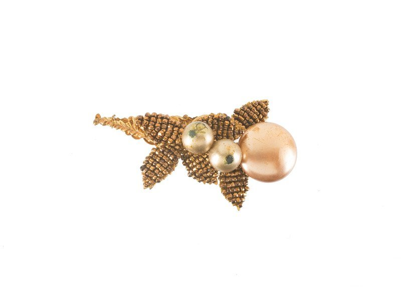 A Miriam Haskell goldtone brooch set with faux pearls.
