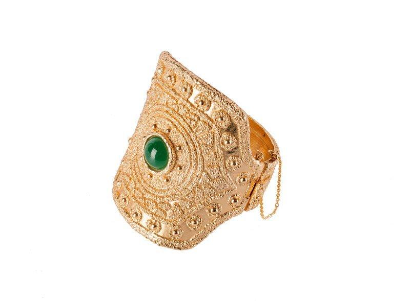 A Napier goldtone solid bracelet, set with a green