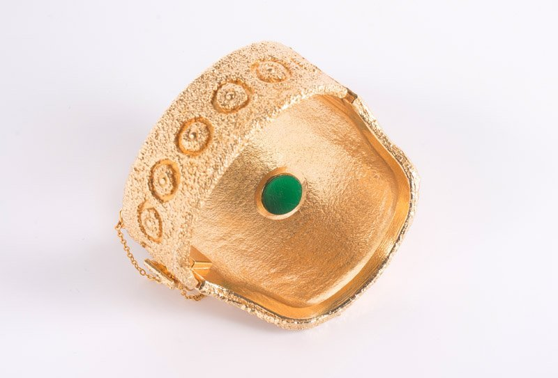 A Napier goldtone solid bracelet, set with a green - 3