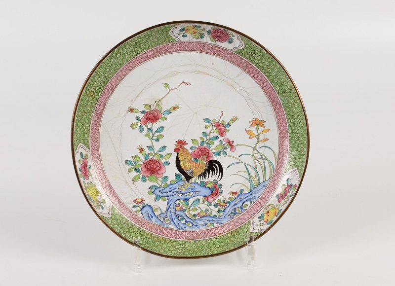 A polychrome enamel plate decorated with roosters.