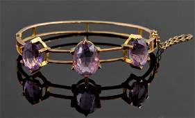 An Edwardian amethyst and gold hinged bangle set with
